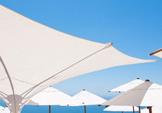 White umbrellas with blue sky in background Royalty Free Stock Photo
