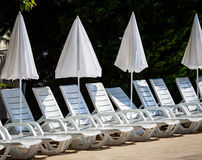 White umbrellas and deck chairs on the beach Royalty Free Stock Photography