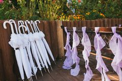 White umbrellas from the sun at a wedding next to a wooden bench decorated with purple ribbons. Horizontal Stock Photography
