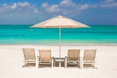 White umbrellas and sunbeds at tropical beach Royalty Free Stock Photography