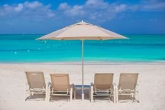 White umbrellas and sunbeds at tropical beach Stock Photos