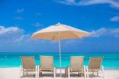 White umbrellas and sunbeds at tropical beach Royalty Free Stock Photo