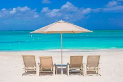 White umbrellas and sunbeds at tropical beach Stock Images