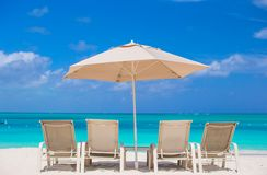 White umbrellas and sunbeds at tropical beach Stock Photo