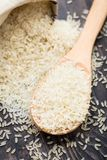 White uncooked rice in a spoon Stock Images