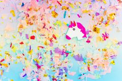 A white unicorn with rainbow horn and confetti top view. Modern art concept. minimalism and candy style royalty free stock photo