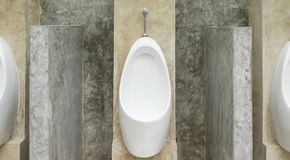 White Urinal Men in Men Public Toilet with Concrete Wall Loft Style. White urinal men with concrete wall loft style for interior design or exterior design. White Royalty Free Stock Photography
