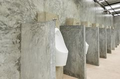 White Urinal Men in Men Public Toilet with Concrete Wall Loft Style. White urinal men with concrete wall loft style for interior design or exterior design. White Stock Images