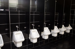 White urinals with black tiles Stock Image