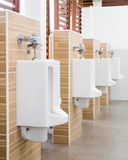 White urinals with ceramic tile on wall. Royalty Free Stock Photography