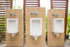 White urinals with ceramic tile on wall. Stock Photo