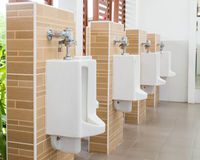 White urinals with ceramic tile on wall. Stock Images