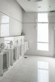 White urinals in clean men public toilet room empty. With big window and light from outside, interior Royalty Free Stock Photography