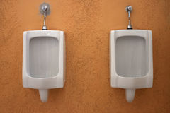 White urinals in the  restroom. Stock Photos