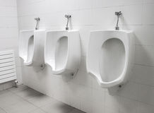 White urinals on wall at public toilet Royalty Free Stock Images
