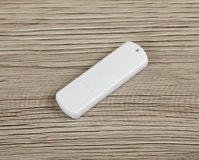White usb flash drive on wooden background. Stock Photos
