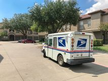 White USPS truck stops at apartment building complex on sunny da. IRVING, TX, USA-SEP 7, 2018:USPS vehicle stopping for package delivery at apartment complex stock image