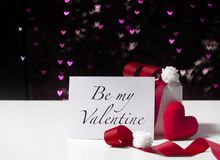 Valentine`s Day card and white gift box with red ribbon and heart shaped fabric on light bokeh background royalty free stock image