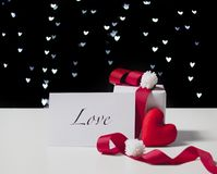 Valentine`s Day card and white gift box with red ribbon and heart shaped fabric on light bokeh background stock images