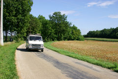 White Van on french country road. White van on rural road in the dordogne, france Royalty Free Stock Image