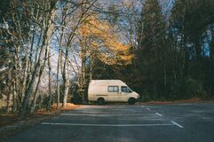 White van parked in the parking lot surrounded by beautiful green trees