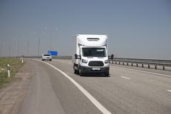 The white van quickly rides along the highway stock photo