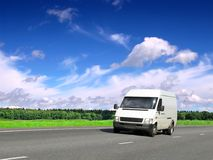 White van speeding on highway. White van on  summer country highway under blue sky Stock Images
