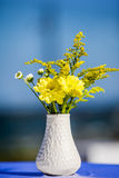 White vase with yellow flowers Royalty Free Stock Image
