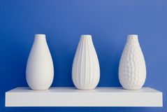 White vases on blue. Three white vases rest on white shelf with blue wall in background stock photo