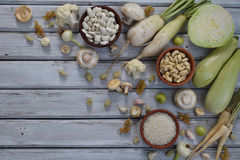 White vegetables and fruits on a wooden background - currant, cauliflower, champignons, radish, parsley, mushrooms, garlic. Onion,. Cabbage mulberry, rice Stock Photos