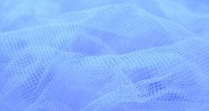 White veil on blue. Close up of white woven veil on blue background stock photo
