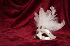 White venetian carnival mask on a red velvet theater curtain. White venetian carnival mask with white feathers seen from the side on a draped red velvet theater Stock Images