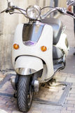 White Vespa  scooter on the street in Italy Stock Photo