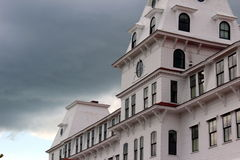 White victorian. Home with black accents against a stormy sky Royalty Free Stock Images