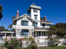 White Victorian House with Picket Fence. California Stick Style Victorian lighthouse built in 1874 with roses growing along a white picket fence Royalty Free Stock Photography