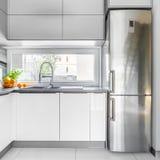 White villa kitchen with window. White villa kitchen interior with high gloss flooring, window and fridge royalty free stock photography
