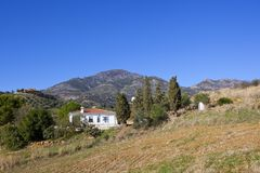 Andalusian farmhouse and mountains under a blue sky. A white villa surrounded by olive groves hills and mountain scenery in picturesque andalusia under a clear Stock Photo