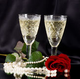 White vine glass with red roses and beads. On black background Stock Photos