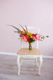 White vintage chair with flowers bouquet Stock Images