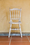 White Vintage chair near yellow old wall Stock Photo
