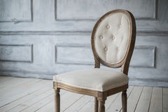 White vintage chair standing in front of a light wall with mouldings on wooden parquet floor. Stock Photo
