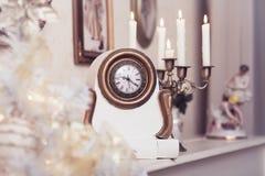 White vintage clock at the burning candles background. Christmas background Stock Image