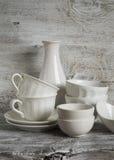 White vintage crockery - ceramic bowl, vase, porcelain tea cups Royalty Free Stock Photo