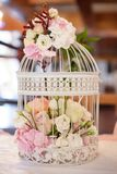 White vintage decorative birdcage filled with white and pastel colored roses and spring flowers. Horizontal shot of wedding romantic decor for guests dinner Royalty Free Stock Image