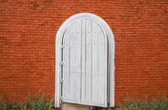 White vintage door on brick wall Stock Images