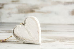 White vintage heart of wood against a white painted wooden backg Stock Images