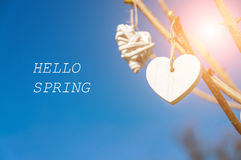 White vintage hearts hanging from tree branch against blue sky. Inscription Hello Spring. Royalty Free Stock Photo