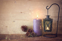 White vintage Lantern with burning candles, pine cones on wooden table and glitter lights background. filtered image Stock Photography