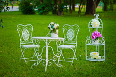 White vintage metal tea table and chairs on a grass in summer park Stock Photos