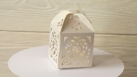 White vintage paper box for gifts turns on a stand against a white wooden wall. 4k video.  stock video